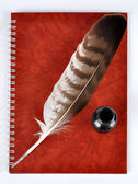 Feather with ink bottle and workbook — Stock Photo