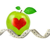 Green apple with heart and measuring tape — Stock Photo