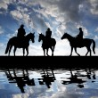 Silhouette cowboys with horses - Stock Photo