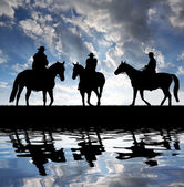 Silhouette cowboys with horses — Stock Photo