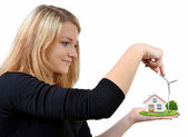 Girl holding in hands wind turbine with the house — Stock Photo