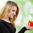 Girl holding in hand red apple — Stock Photo