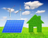 Green grass house symbol with solar panel and wind turbines — Stock Photo
