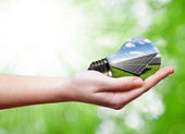 Bulb with of solar panel in hand — Stock Photo