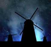 Silhouettes of windmills on night sky — Stock Photo