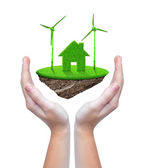 Small island with green house and wind turbines in hands — Foto de Stock