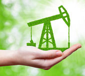 Green oil pump in hand — Stock Photo