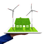 Hand holding a tablet with green house and wind turbines — Stock Photo