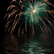 Yellow fireworks on the night sky over the water — Stock Photo