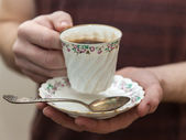 Porcelain cup with coffee in hand of a young man — Stock Photo