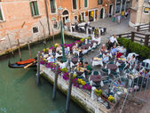 Venice, Italy, June 21, 2012 . Tourists sitting in a summer cafe on the canal bank — Stock Photo
