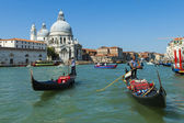 Venice, Italy, Tourists ride on a gondola through a channel — Stock Photo