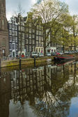 Amsterdam, The Netherlands, April 13, 2012 . Houses on the canal reflected in its water — Stockfoto