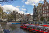 Amsterdam, The Netherlands April 14, 2012 . Pleasure ship sails through the channel in the center of town past the old houses of traditional architecture — Stock Photo