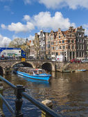 Amsterdam, The Netherlands April 16, 2012 . Pleasure ship sails through the channel in the center of town past the old houses of traditional architecture — Stock Photo