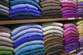 Piles of multi-colored cashmere products on shelves in the shop — Stock Photo