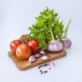 Fresh vegetables and greens for salads on the table — Stock Photo