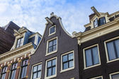 Amsterdam, the Netherlands, Typical architectural details of facades of the town houses constructed of the burned brick — Foto Stock