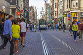 Amsterdam, Netherlands, on July 7, 2014. Tourists and citizens go on the narrow brisk street with tram ways — Stock Photo