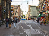 Amsterdam, Netherlands, on July 7, 2014. Tourists and citizens go on the narrow brisk street with tram ways — Foto de Stock