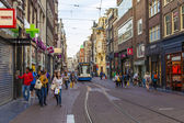Amsterdam, Netherlands, on July 7, 2014. Tourists and citizens go on the narrow brisk street with tram ways — Photo