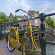 Amsterdam, Netherlands, on July 7, 2014. Bicycle on the bank of the channel. The bicycle is very popular type of transport in Holland — Stock Photo