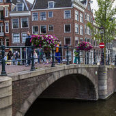 Amsterdam, Netherlands, on July 7, 2014. Typical urban view with old houses on the bank of the channel and the stone bridge — Photo