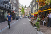 Amsterdam, Netherlands, on July 7, 2014. Tourists and citizens sit at cafe little tables on the street — Foto de Stock