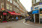 Amsterdam, Netherlands, on July 7, 2014. Tourists and citizens sit at cafe little tables on the street — Photo