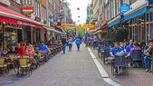 Amsterdam, Netherlands, on July 7, 2014. Tourists and citizens sit at cafe little tables on the street — Foto Stock