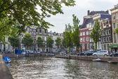 Amsterdam, nederland, op 7 juli 2014. typisch stedelijke weergave met huizen aan de oever van het kanaal en de oude stenen brug — Stockfoto