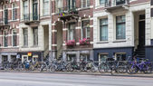 Amsterdam, Netherlands, on July 10, 2014. Bicycles are parked on the city street on the bank of the channel — Stock Photo