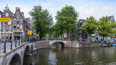Amsterdam, Netherlands, on July 7, 2014. Typical urban view with houses on the bank of the channel and the old stone bridge — Stock Photo