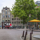 Amsterdam, Netherlands, on July 7, 2014. Tourists and citizens sit at cafe little tables on the street — Stock Photo