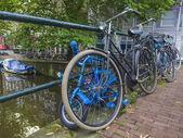 Amsterdam, Nizozemsko, na 10 července 2014. jízdní kola jsou zaparkované na ulici města na břehu kanálu — Stock fotografie