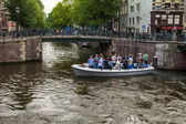Amsterdam, Netherlands, on July 10, 2014. Walking boat is moving by the channel coast — 图库照片