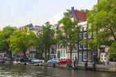 Amsterdam, Netherlands, on July 10, 2014. Typical urban view with houses on the bank of the channel — Stock Photo