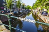 Amsterdam, Netherlands, on July 10, 2014. Typical urban view with old buildings on the bank of the channel and boats moored at bank — Stock Photo