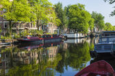 Amsterdam, Netherlands, on July 10, 2014. Inhabited boats at the channel coast — Stock Photo
