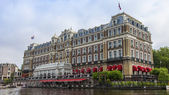 Amsterdam, Netherlands, on July 10, 2014. View of the river bank Amstel. Vintage mill — Stock Photo