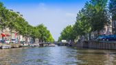 Amsterdam, Netherlands, on July 10, 2014. A typical urban view with old buildings on the bank of the channel — Stock Photo