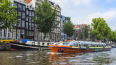 Amsterdam, Netherlands, on July 10, 2014. Walked boat is floating by the channel — Stock Photo