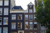 Amsterdam, Netherlands, on July 10, 2014. Typical architectural details of old buildings on the bank of the channel — Stock Photo