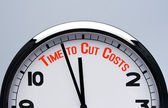 Relógio com tempo de palavras para cortar custos. é hora de cortar o conceito de custos. — Foto Stock