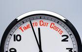 Reloj con el tiempo de palabras para reducir costos. hora de cortar costos concepto. — Foto de Stock