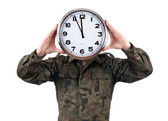 Soldier with analog clock over his face. Deadline concept isolated on white background. — Stok fotoğraf