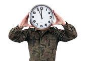 彼の顔の上にアナログ時計と兵士。白い背景で隔離の締め切りコンセプト. — ストック写真