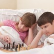 Children play chess in a bed — Stock Photo #13451191