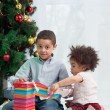 Brother and sister holding Christmas gifts — Stock Photo #13451197