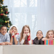 Smiling Children holding Christmas gifts — Stock Photo #13451209